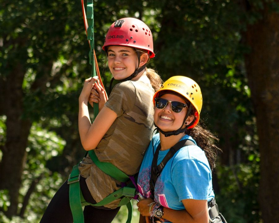 Camper and staff in climbing harnesses
