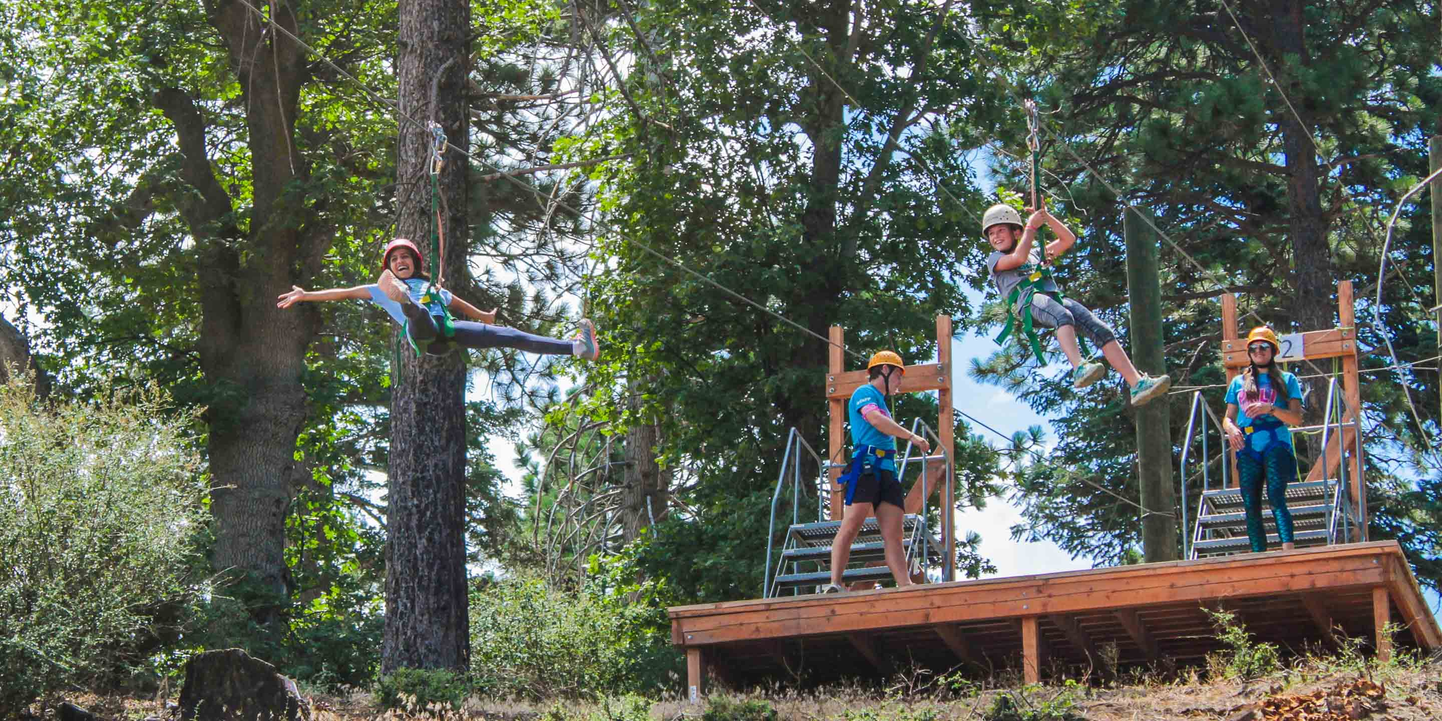 Two campers on zip line with staff in background