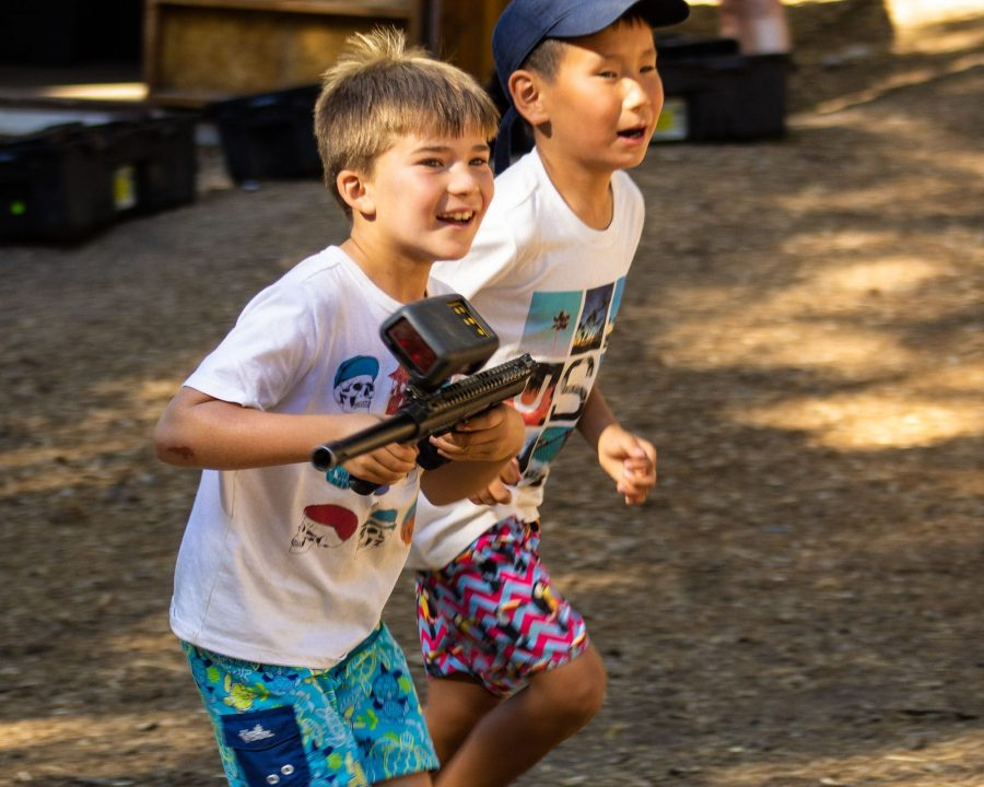 Two boys running while playing laser tag